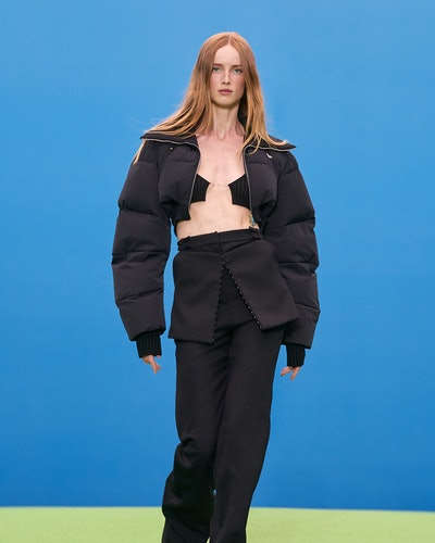 Model wears gorpcore-inspired trousers and a black puffer jacket during Jaquemus' Fall/Winter 2021 r...