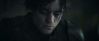 Robert Pattinson wearing the batsuit in the rain in The Batman