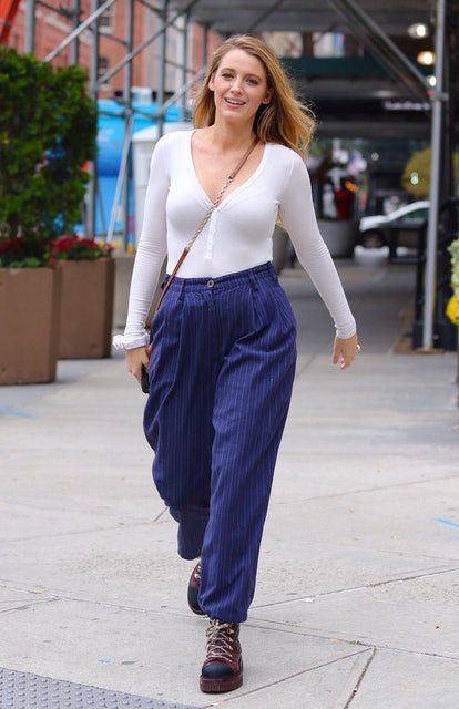 Blake Lively in New York City on Oct. 13, 2021, wearing a white long-sleeve shirt, blue pants, and c...