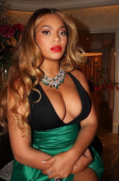 Beyonce in red lipstick with green necklace and dress