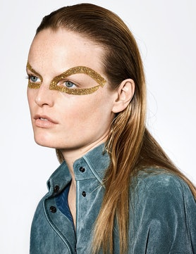 a model with a ring of gold glitter paint around her eye