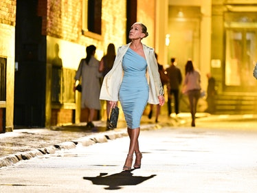 Carrie Bradshaw walking in a tight baby blue dress and looking up