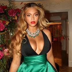 Beyonce in long golden waves sitting on table with red lipstick and green dress