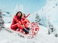 Two women sit in sleighs from FUNBOY's Winter 2021 collection on a snowy mountain.
