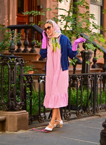 Carrie Bradshaw wearing a Batsheva prairie dress and smoking a cigarette outside
