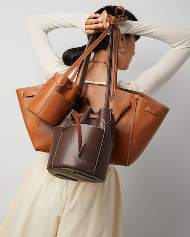 Model holds Anya Hindmarch's biodegradable leather bags.