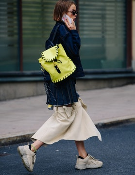 a woman walking down the street talking on a cell phone, with a neon backpack slung over her shoulde...