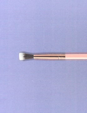 a pink makeup brush against a lavender background