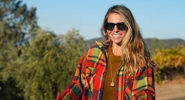 Allison Carrol wearing a plaid flannel jacket and sunglasses holding a large plastic bin full of oli...