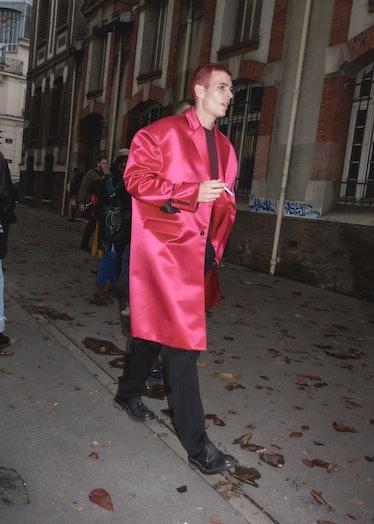 Showgoer at Paris Fashion Week in pink satin coat.