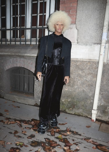 Showgoer at Paris Fashion Week wears full black look with corset.