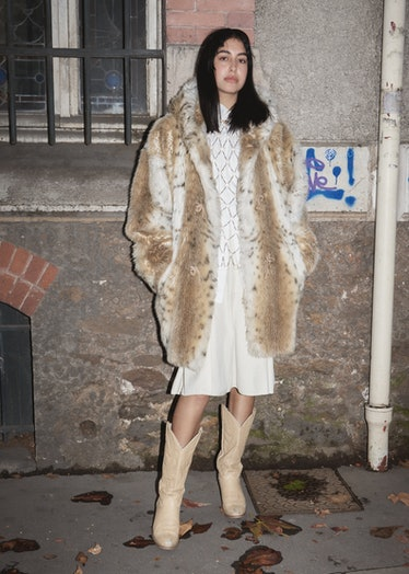 Showgoer at Paris Fashion Week wears fuzzy leopard coat, white dress, and cowboy boots.
