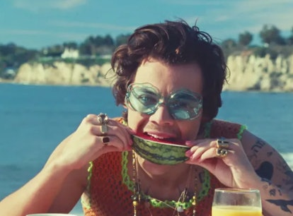 """Harry Styles biting into a juicy slice of watermelon in the """"Watermelon Sugar"""" music video."""