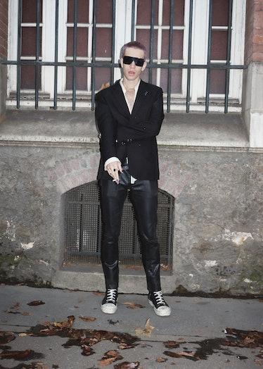 Showgoer at Paris Fashion Week wears black suit.