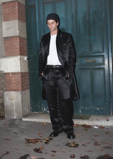 Showgoer at Paris Fashion Week wears black satin suit.