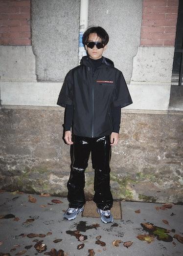 Showgoer at Paris Fashion Week wears all black Prada ensemble.