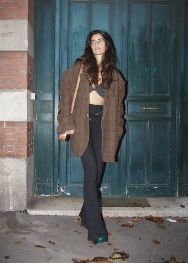 Showgoer at Paris Fashion Week wears oversized brown jacket and black pants.