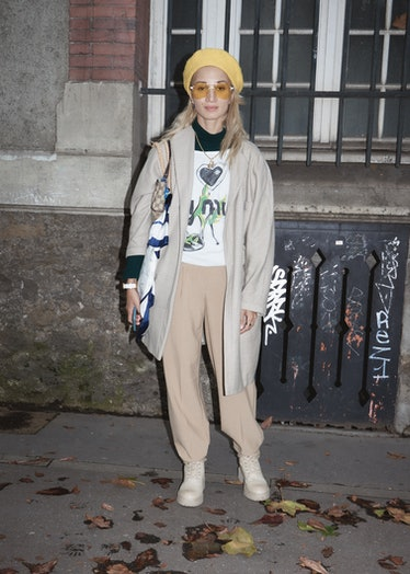 Showgoer at Paris Fashion Week in tan pants and jacket and yellow beret.