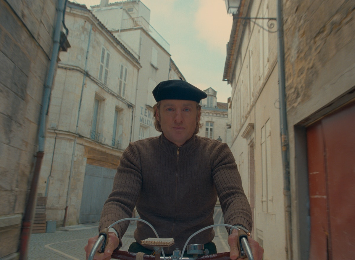 Owen Wilson rides a bike on a carefully researched street.