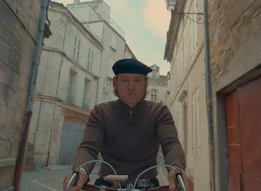 Owen Wilson bikes down a carefully considered street.