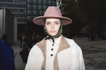Street style at Paris Fashion Week: Showgoer wears pink hat with scarf and white sweater.