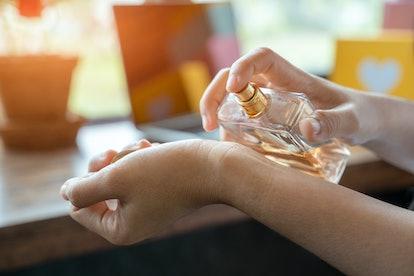 Woman spraying wrist with perfume