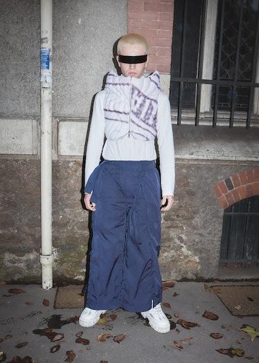 Showgoer at Paris Fashion Week wears wraparound sunglasses and blue parachute pants.