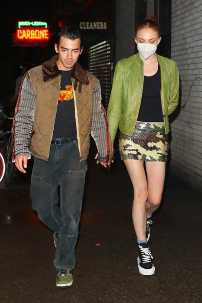 Sophie Turner wears camo print sequined skirt, black tank top, green leather jackets, and Louis Vuit...