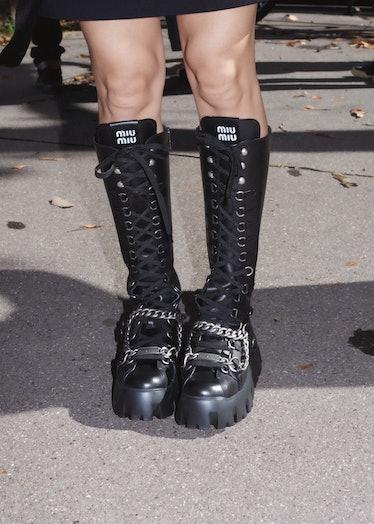 Showgoer in black Miu Miu combat boots outside the Miu Miu spring 2022 show at Paris Fashion Week.