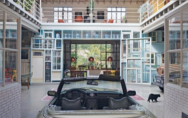 the atrium of a modern house in the netherlands, with a car parked in the center and art objects all...