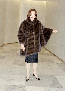 Tilda Swinton wearing a fur coat in a marble hallway