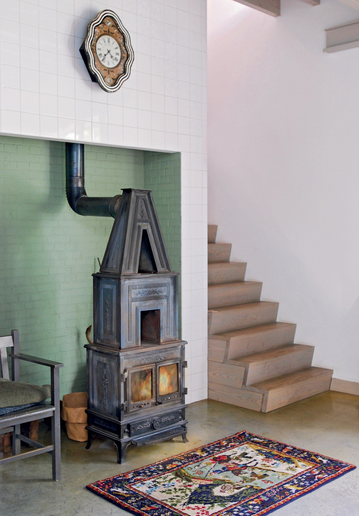 a wood-burning stove at the bottom of a modern staircase