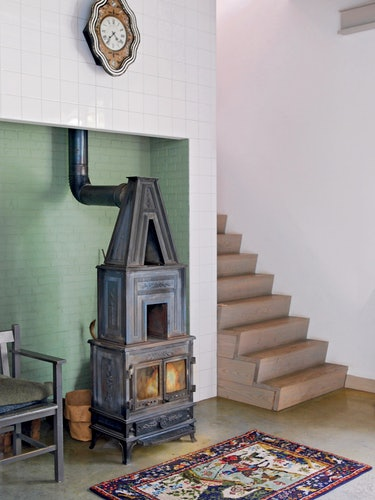 a wood burning stove at the bottom of a modern staircase