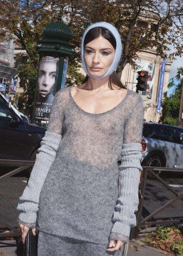 Angela Rozas Saiz wears blue knit bonnet and gray sweater outside Miu Miu spring 2022 show at Paris ...