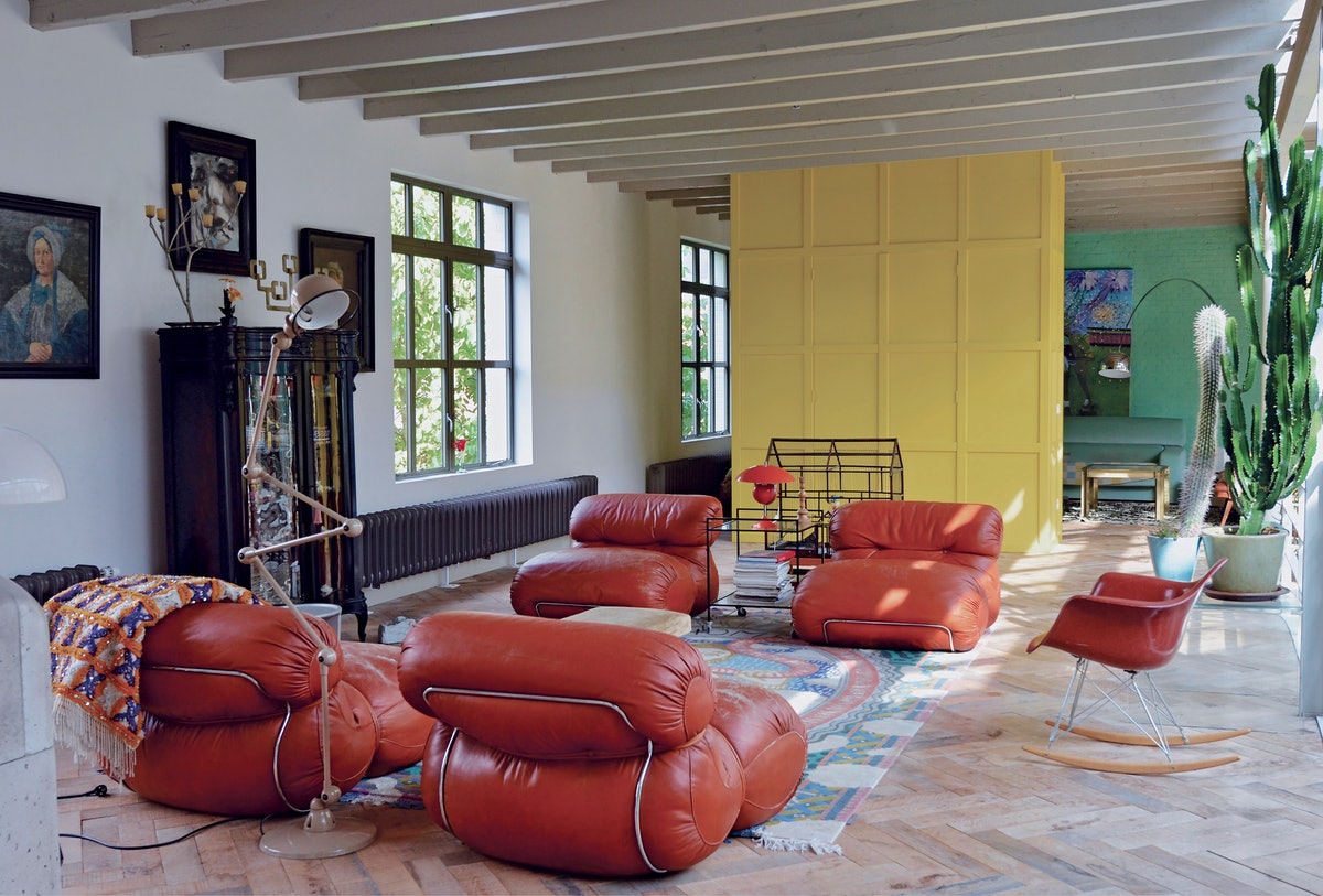a living room with a yellow wall and bulbous red leather sofas