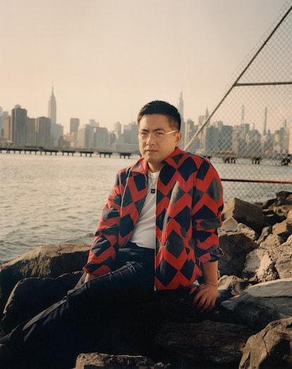 Bowen Yang wears a Bode jacket; Sunspel T-shirt; Berluti pants; his own  glasses and jewelry.
