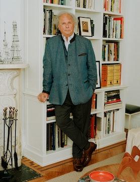 Graydon Carter leaning against a bookshelf in his office