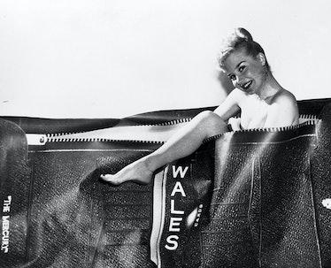 Cindy Adams posing inside a large wallet.