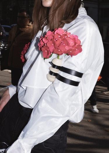 Showgoer wears flower accessories outside Miu Miu spring 2022 show at Paris Fashion Week.