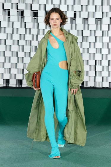 Model walks runway in teal body suit and green jacket from Stella McCartney spring 2022 collection.