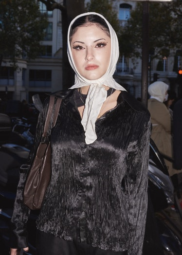 Showgoer in brown silk and white head scarf at Paris Fashion Week.