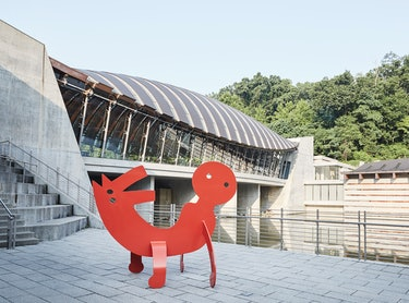 A red metal keith haring sculpture on a museum terrace