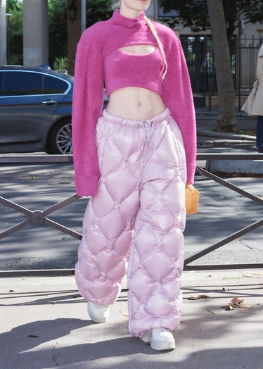 Showgoer wears pink sweater and puffer pants outside Miu Miu spring 2022 show at Paris Fashion Week.