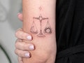 An image of a Libra Tattoo with a simple scale balancing a crescent moon and sun.