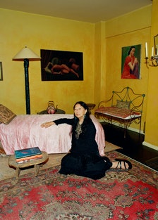 Nian fish, wearing an all-black outfit, reclines on the floor against a bed covered in a pink quilt.