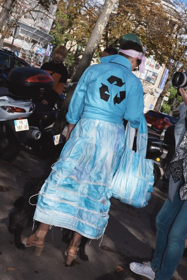 Showgoer in pale blue skirt and jacket with recycle symbol on it at Paris Fashion Week.