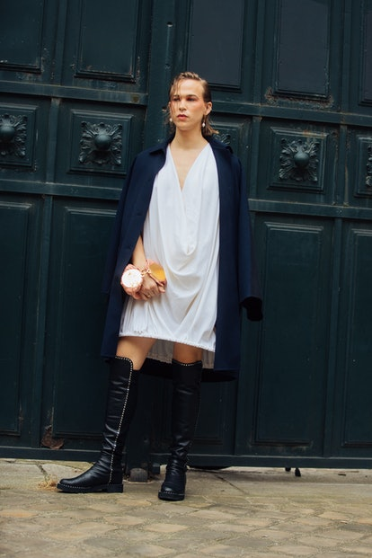 Tommy Dorfman wears a blue jacket with a white dress and knee-high black boots at the Loewe show on ...