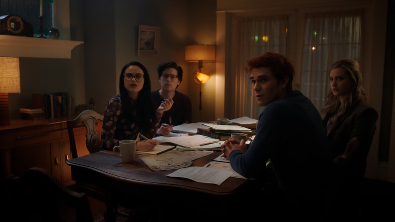 The core four of Riverdale sits at a table looking towards the camera in a scene from Riverdale Seas...