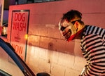 Two girls react as a character with a chain saw approaches their car at a drive-thru Halloween exper...