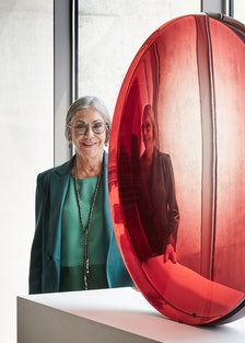 """Alice Walton with Frederick Eversley's """"Big Red Lens,"""" 1985."""